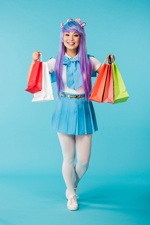 Full length view of Asian anime girl holding shopping bags on blue background
