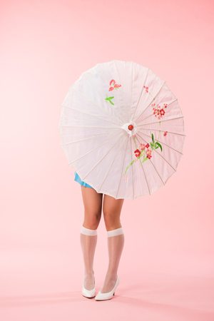 Full length view of girl in white knee socks holding paper umbrella on pink background