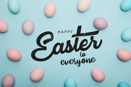 top view of painted multicolored eggs on blue background with happy Easter to everyone lettering
