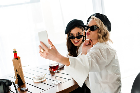 Elegant brunette and blonde women in black berets and sunglasses drinking red wine and taking selfie while pouting lips and sticking out tongue