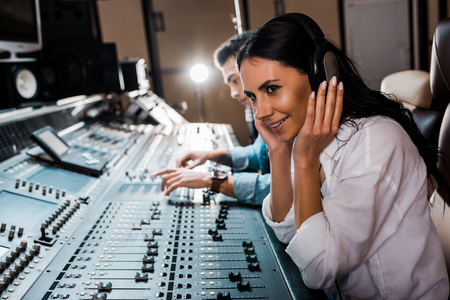 Sound producer in headphones near mixed racial friend working at mixing console Banco de Imagens