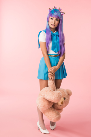 Full length view of Asian anime girl holding teddy bear on pink background