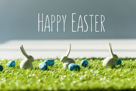 Decorative bunnies on green grass near blue quail eggs with happy Easter lettering Stockfoto - 121433008