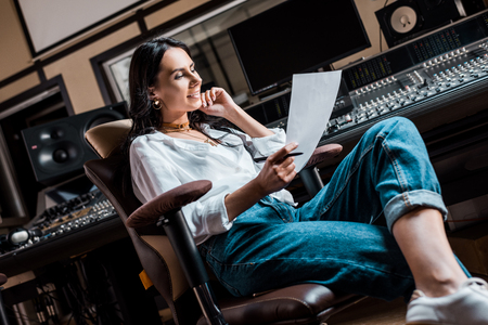Beautiful smiling sound producer sitting in office chair near mixing console in recording studio Stock Photo