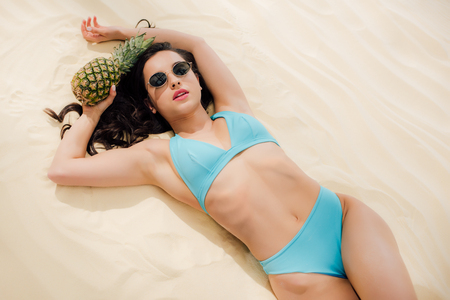 Attractive girl in blue Bikini and sunglasses posing with pineapple while lying on sandy beach