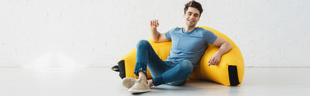 Panoramic shot of happy man sitting near yellow bean bag chair at home Stock Photo