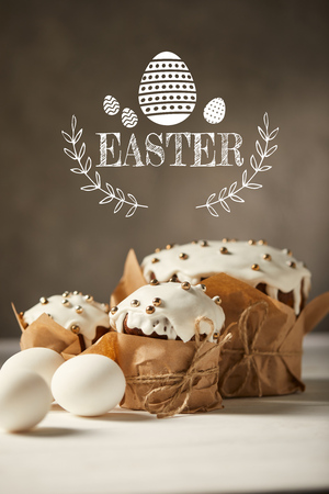 Traditional Easter bread in craft paper and white chicken eggs on white table with Easter lettering