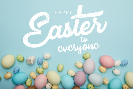 Top view of painted multicolored eggs scattered near decorative bunny on blue background with happy Easter to everyone lettering Imagens