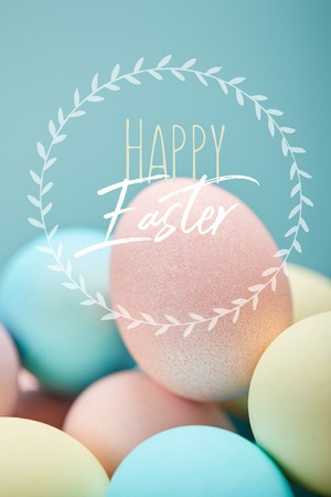 Pile of multicolored painted chicken eggs with happy Easter lettering in circle on blue background 版權商用圖片