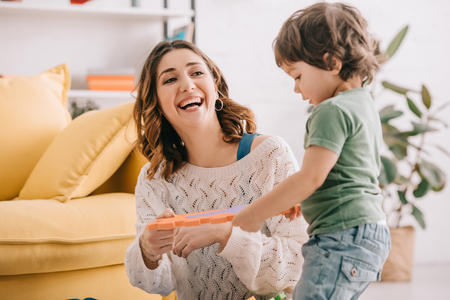 Laughing mother playing with little son in living room