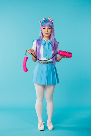 Full length view of Asian anime girl with telephone on blue background