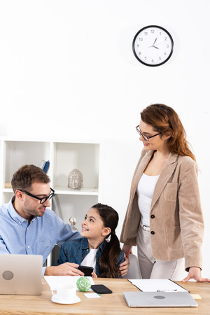 Father in glasses holding smartphone near happy daughter in office