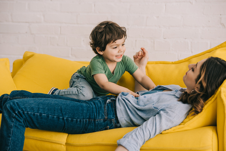 little boy sitting on tired mother while she lying on yellow sofa in living room Stock Photo