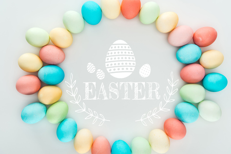 Top view of round frame made of painted multicolored eggs with Easter white lettering