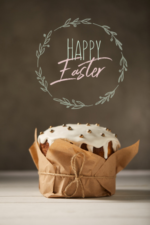 Traditional decorated Easter cake in craft paper with happy Easter lettering in circle on brown background