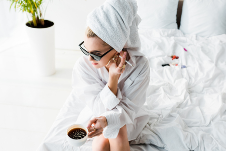 young stylish woman in jewelry and sunglasses with towel on head and cup of coffee smoking cigarette while sitting on bed