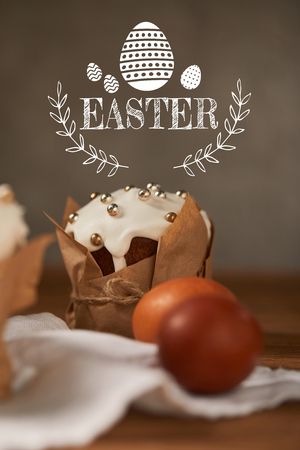 Selective focus of traditional Easter cake in craft paper and chicken eggs on napkin with Easter lettering Stock Photo