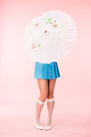Full length view of girl in white knee socks holding paper umbrella on pink background