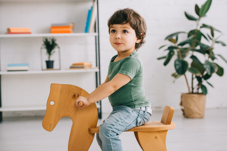 Child sitting on wooden rocking horse in living room
