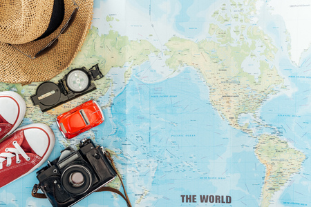 Top view of gumshoes, straw hat, sunglasses, film camera, toy car and compass on world map Stock Photo