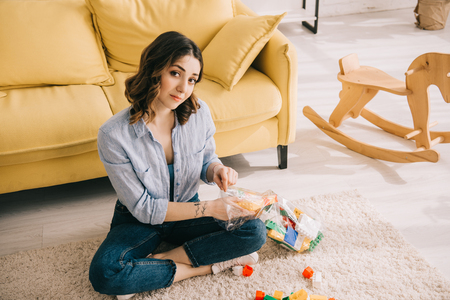 Woman with toy blocks sitting with crossed legs on carpet