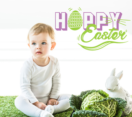 child sitting near savoy cabbage and decorative bunny on green grass with happy Easter lettering