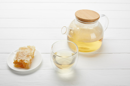 Teapot with organic herbal tea, glass and honeycomb on white wooden table
