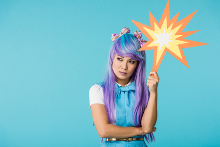 Dissatisfied Asian anime girl in wig looking away isolated on blue background Stockfoto