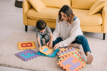 Mother and son playing with alphabet puzzle mat on carpet