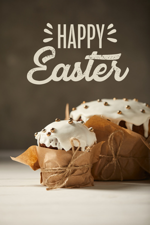 Traditional decorated Easter cakes in craft paper on white table with happy Easter lettering on brown background Фото со стока