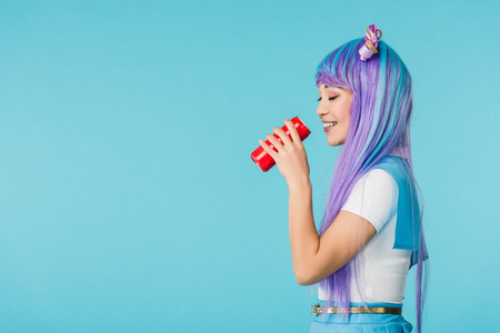 Side view of anime girl drinking beverage isolated on blue background