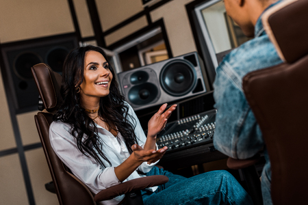 Cheerful attractive sound producer talking to mixed race colleague in recording studio Foto de archivo - 121433433