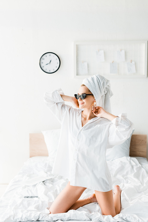 happy young stylish woman in shirt, sunglasses, jewelry and with towel on head sitting on bed