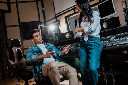 Two young multicultural sound producers talking near mixing console in recording studio