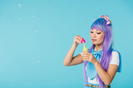 Asian anime girl in purple wig with soap bubbles isolated on blue background