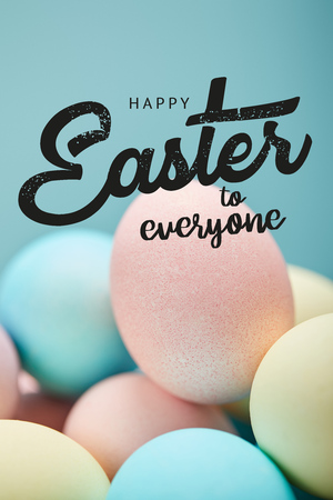 Pile of multicolored painted chicken eggs with happy Easter to everyone lettering on blue background