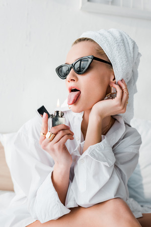 Young stylish woman in jewelry and sunglasses with towel on head sticking out tongue near fire from lighter