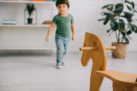 Selective focus of toddler boy in green t-shirt and wooden rocking horse Stock Photo
