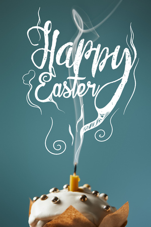 Selective focus of traditional Easter cake with fireless candle and smoke on blue background with happy Easter lettering Фото со стока