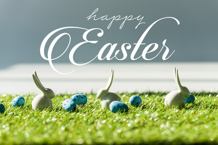 decorative rabbits on green grass near blue quail eggs with happy Easter lettering