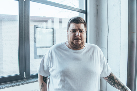 Overweight tattooed man in white t-shirt looking at camera at gym