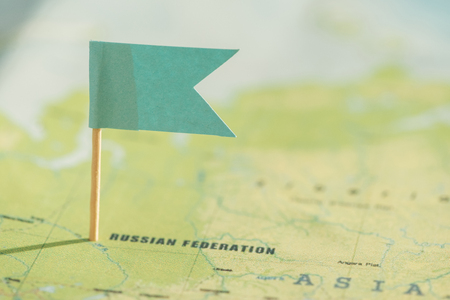 Selective focus of world map and little green flag Stockfoto