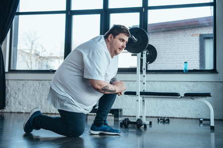 Overweight tattooed man in white t-shirt stretching at sports center