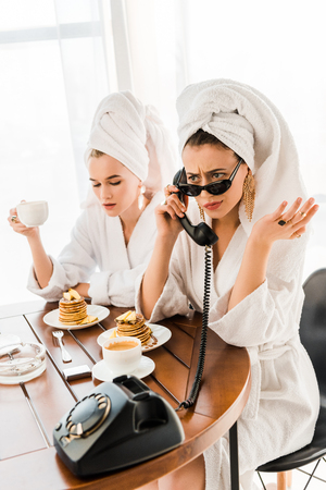 Stylish dissatisfied woman in bathrobe, sunglasses and jewelry with towel on head talking on retro telephone while having breakfast with friend