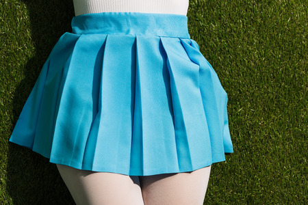 Cropped view of girl in blue skirt lying on grass