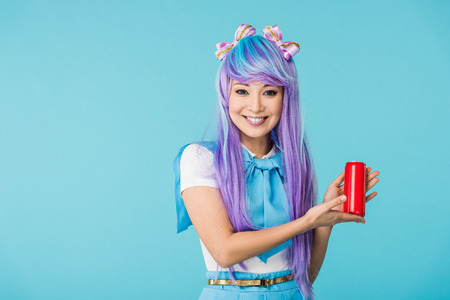 Smiling Asian anime girl in wig holding can with beverage isolated on blue background