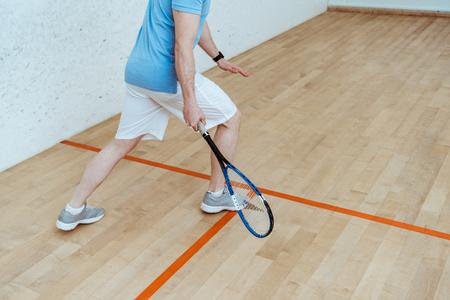 Vue recadrée d'un sportif en short blanc jouant au squash