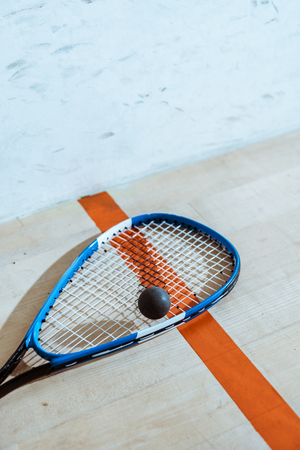One squash racket and ball on wooden surface 写真素材
