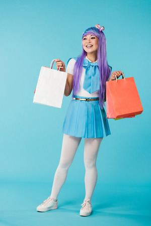 Full length view of Asian anime girl holding shopping bags on blue background