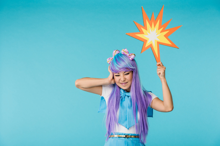 Irritated Asian anime girl in wig posing on blue background Stock Photo